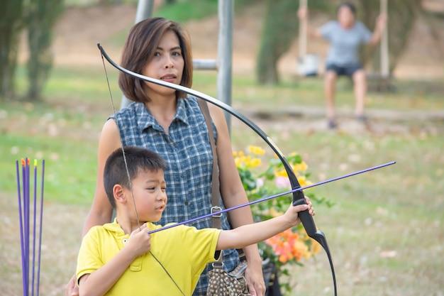 Aziatische jongens die een boog in kampavontuur houden en de vrouw achter onscherpe boom als achtergrond. Premium Foto