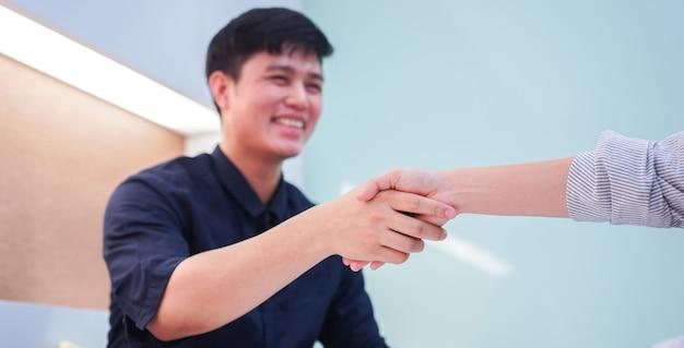 Aziatische kandidaat-man de hand schudden met manager na voltooide contract in prive-conferentieruimte Premium Foto