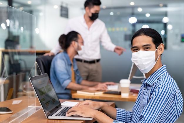 Aziatische kantoormedewerker met beschermend gezichtsmasker werken in nieuw normaal kantoor Premium Foto