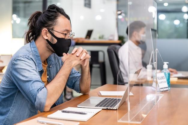 Aziatische kantoormedewerker zakenman draagt beschermend gezichtsmasker werk in nieuw normaal kantoor Premium Foto