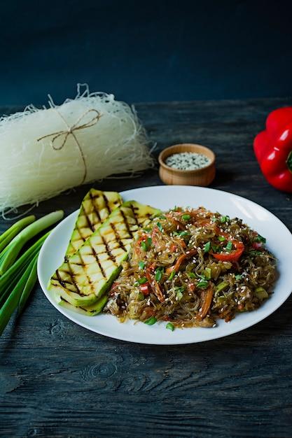Aziatische keuken. cellofaan noedels versierd met groenten, groenten. funchoza. goede voeding. gezond eten. uitzicht van boven. donkere houten achtergrond. Premium Foto