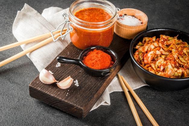 Aziatische keuken. gefermenteerd voedsel. traditioneel koreaans gerecht: kimchi-koolkool met traditionele kimchi-saus van hete rode chili, knoflook, kruiden, zout. zwarte stenen tafel. Premium Foto