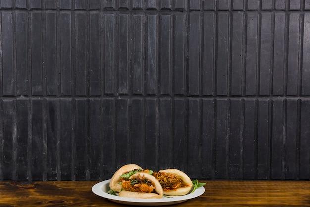 Aziatische keuken gua bao gestoomde broodjes met groente op houten tafel tegen zwarte muur Gratis Foto