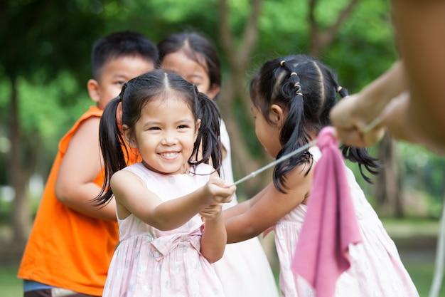 Aziatische kinderen die pret hebben om touwtrekwedstrijd met touw samen in het park te spelen Premium Foto