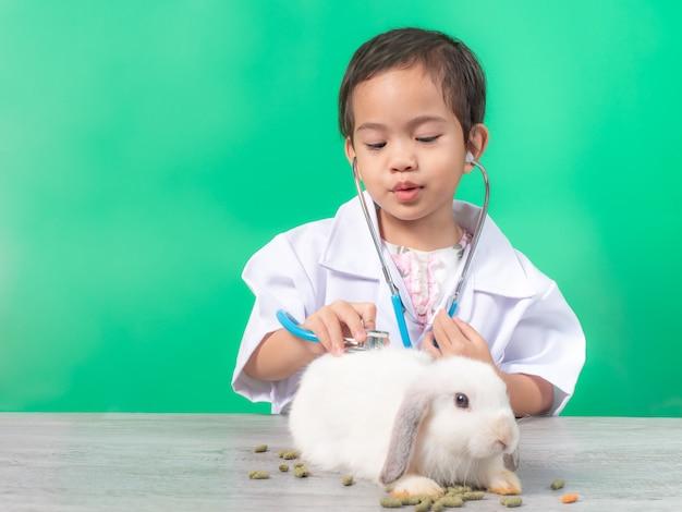 Aziatische kleine schattige meisje 3 jaar oude rol spelen dieren arts arts. Premium Foto