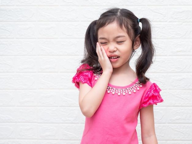 Aziatische kleine schattige meisje van 6 jaar heeft kiespijn en houdt haar wang vast. Premium Foto