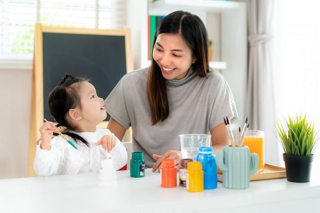Aziatische kleuterschool schoolmeisje met moeder schilderij gips pop met acryl aquarel verf in de woonkamer thuis. thuisonderwijs en afstandsonderwijs. Premium Foto