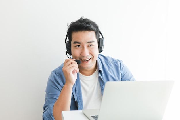 Aziatische knappe man in blauw shirt met behulp van laptop met hoofdtelefoon praten glimlach en blij gezicht Premium Foto