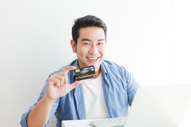 Aziatische knappe man in blauw shirt met creditcard met laptopcomputer online winkelen Premium Foto