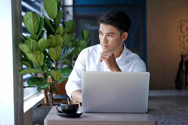 Aziatische knappe zakenman of beambte die bij coffeeshop werken Premium Foto