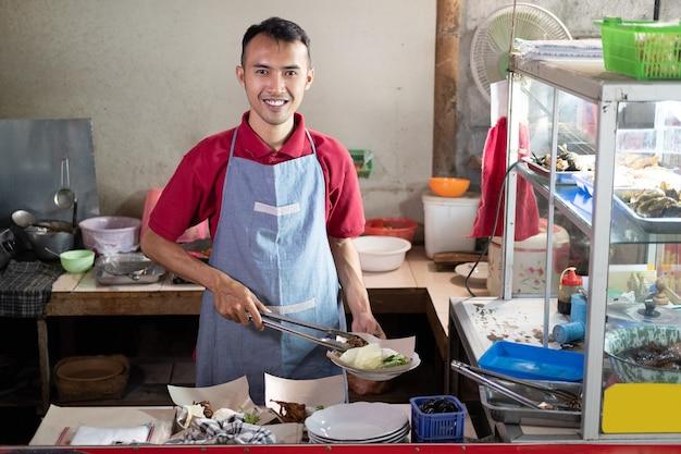 Aziatische kraamkelners houden een tang vast terwijl ze bijgerechten bereiden voor de bestellingen van klanten bij de kraam Premium Foto