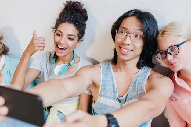 Aziatische langharige jongen die selfie met vrienden die zwarte telefoon houden en glimlachen. grappige blonde vrouw in glazen met plezier met krullende jonge dame en brunette student. Gratis Foto