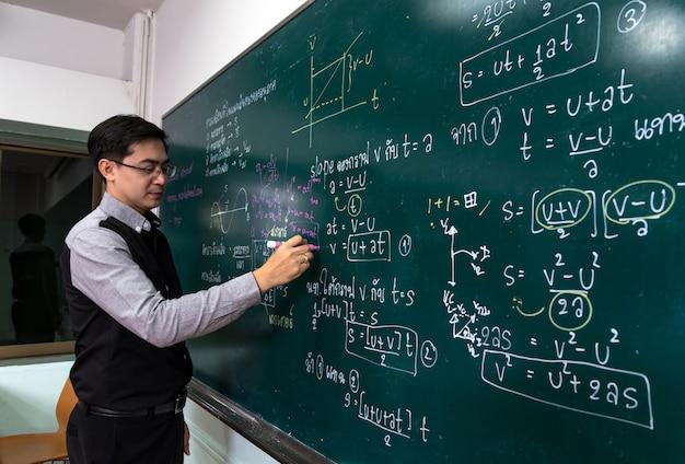 Aziatische leraar die de natuurkunde formular in thaise taal op zwarte raad schrijft Premium Foto