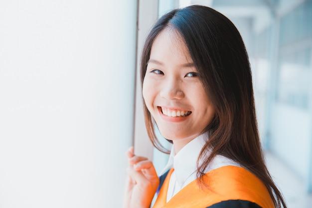 Aziatische leuke afstuderen van het vrouwenportret, de universiteit van thailand. Premium Foto