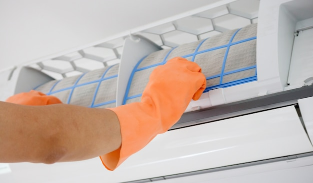 Aziatische man airconditioner vuil filter schoonmaken Premium Foto