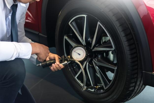 Aziatische man auto inspectie holdind tablet voor meten hoeveelheid opgeblazen rubber banden auto. close-up hand houden machine opgeblazen manometer voor auto bandenspanningsmeting voor auto Premium Foto