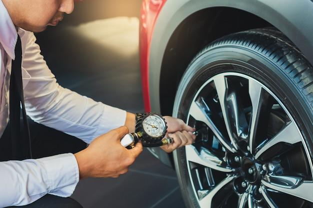 Aziatische man auto-inspectie maatregel hoeveelheid opgeblazen rubber banden auto. Premium Foto