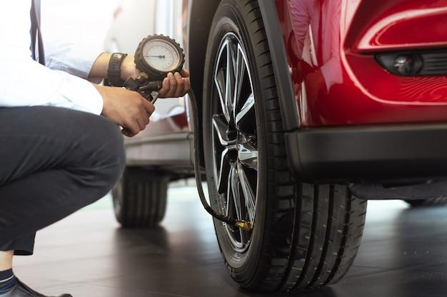 Aziatische man auto-inspectie meet de hoeveelheid opgeblazen rubberbanden auto. Premium Foto
