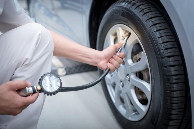 Aziatische man auto inspectie meet hoeveelheid opgeblazen rubber banden auto Premium Foto