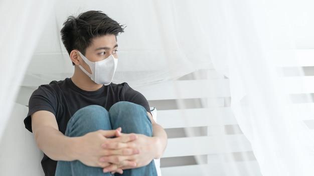 Aziatische man draagt een gezichtsmasker om zich ziek te voelen, hoofdpijn en hoest vanwege coronavirus covid-19 in quarantainekamer Gratis Foto