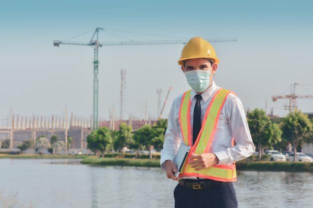 Aziatische man draagt medisch masker met tablet werkt aan bouwplaats nieuw normaal beschermt coronavirus covid 19 Premium Foto