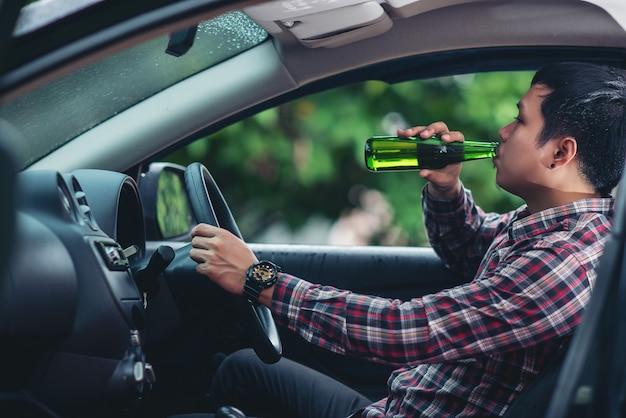 Aziatische man drinkt een bierfles terwijl het besturen van een auto Gratis Foto