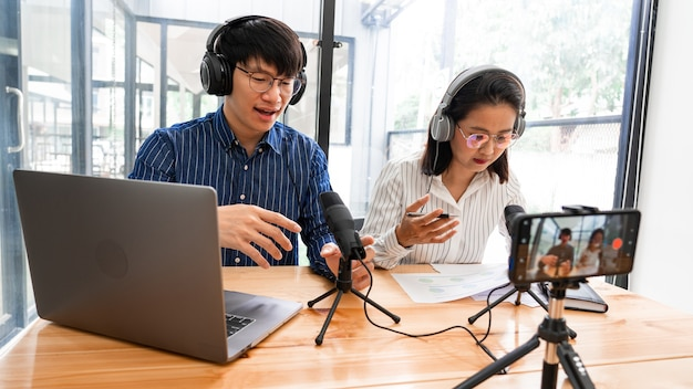 Aziatische man en vrouw podcasters in hoofdtelefoons opnemen van inhoud met collega Premium Foto