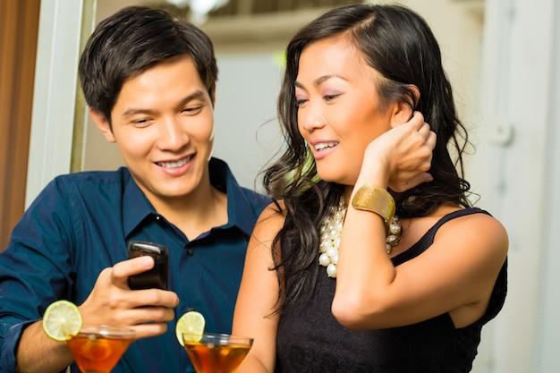 Aziatische man flirt met vrouw in bar Premium Foto