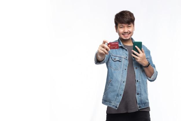 Aziatische man in smileygezicht met creditcard en smartphone Premium Foto
