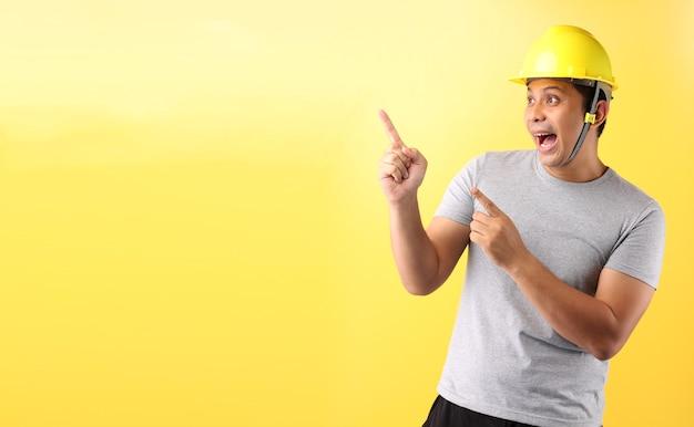 Aziatische man industrie werknemer of ingenieur werkt een architect bouwer wijzende vinger op gele achtergrond. Premium Foto