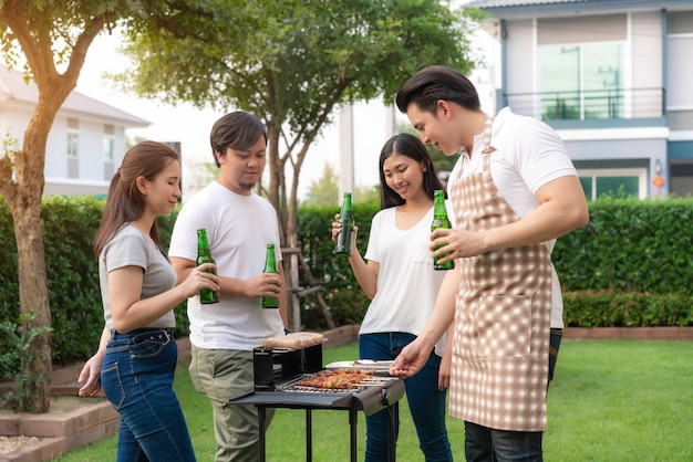 Aziatische man koken barbecue grill en worst voor een groep vrienden om te eten partij in de tuin thuis. Premium Foto