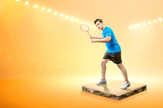 Aziatische man met badminton racket houden shuttle en klaar in dienen positie Premium Foto