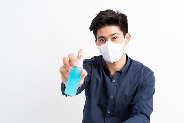 Aziatische man met gezichtsmasker met alcohol voor het wassen van handen om coronavirus covid-19 in quarantainekamer te beschermen Gratis Foto