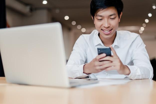 Aziatische man op kantoor gebruikt telefoon en laptop Premium Foto