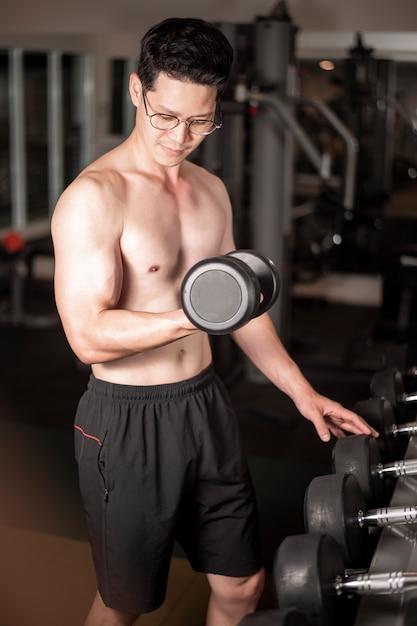 Aziatische man werkt in fitness gym Premium Foto