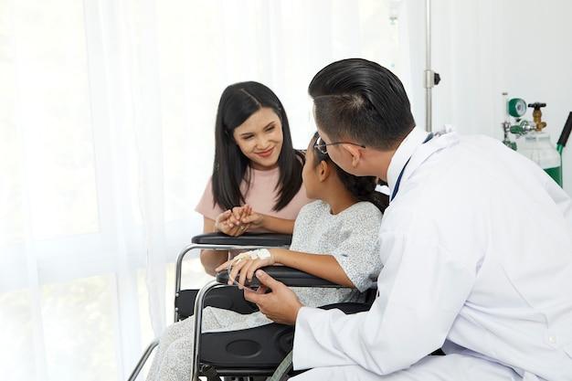 Aziatische mannelijke arts die aan jonge kindrolstoel en moeder, de zorg van het conceptaziathuis spreekt Premium Foto
