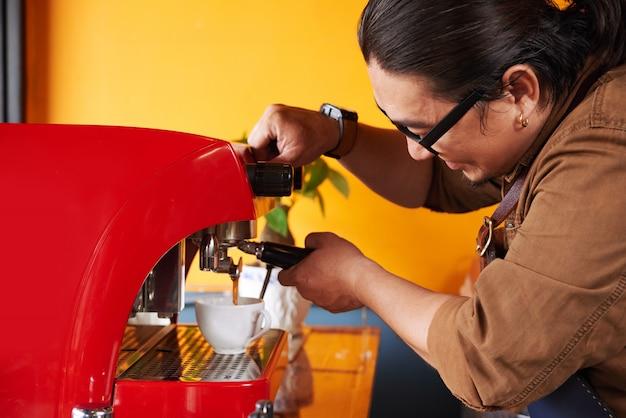 Aziatische mannelijke barista die kop van koffie op espressomachine maken Gratis Foto