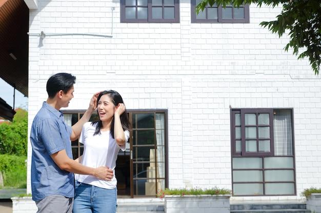 Aziatische mannelijke en vrouwelijke koppels staan, knuffelen en glimlachen gelukkig voor het nieuwe huis. het concept van een huwelijksleven beginnen om een gelukkig gezin te stichten. kopieer ruimte Premium Foto