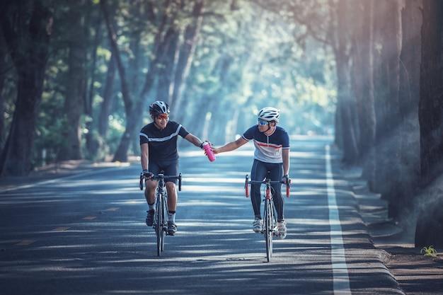 Aziatische mannen fietsen 's morgens racefiets en delen water met elkaar Premium Foto