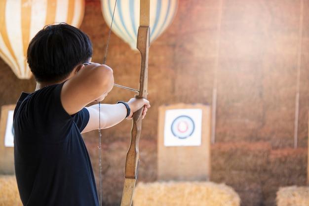Aziatische mannen schieten boogschutter focus op doel objectieve bestemming win uitdaging Premium Foto