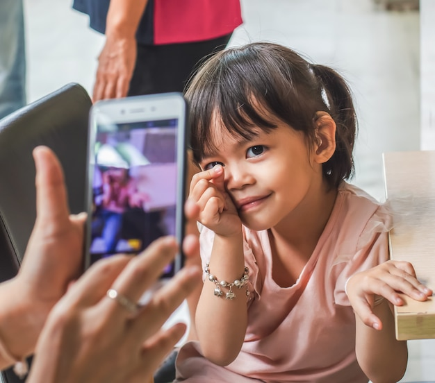 Aziatische meisje neemt een foto met een smartphone. Premium Foto