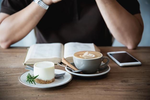 Aziatische mens die een koffie drinkt en een boek leest Gratis Foto