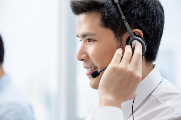 Aziatische mens die in call centrebureau werkt Premium Foto