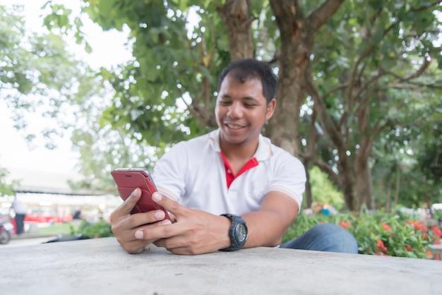 Aziatische mens die mobiele telefoon op de lijst in het park met behulp van dichtbij de avondtijd. hij ziet er gelukkig uit. concept ontspannen mensen die mobiele apparaten werken. Premium Foto