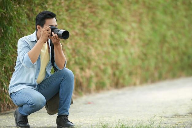 Aziatische mens die neer in park buigt en foto's met digitale camera neemt Gratis Foto