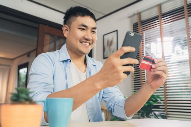 Aziatische mens die smartphone voor online het winkelen en creditcard in internet gebruiken bij woonkamerhuis Gratis Foto