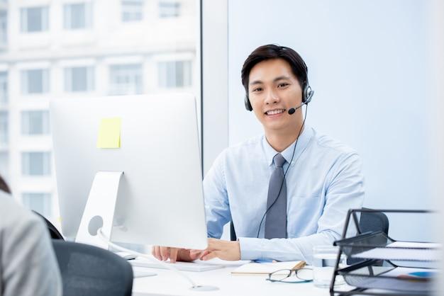 Aziatische mens die telemarketer in offfice werkt Premium Foto