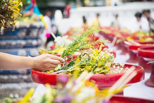 Aziatische mens die verse gele bloemen voor participatie lokale traditionele boeddhistische ceremonie houden, mensen met godsdienstrelatie Gratis Foto