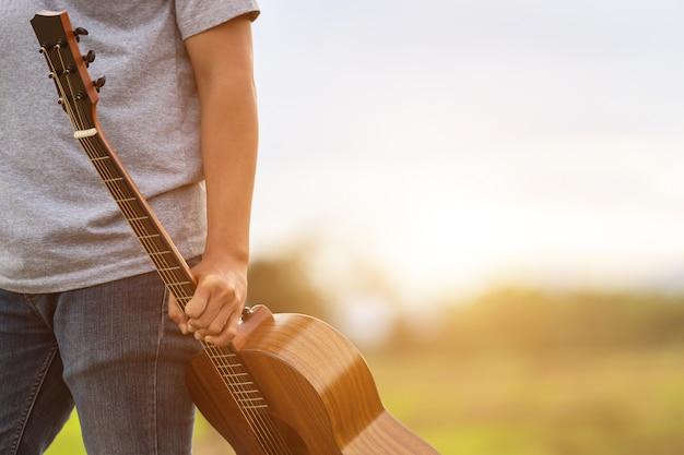 Aziatische mens het spelen gitaar bij het groene padieveld in de zonsondergangtijd Premium Foto