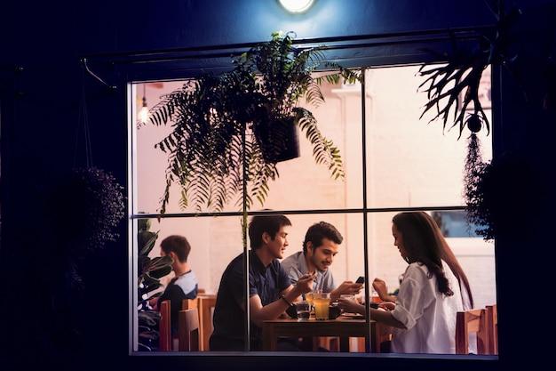 Aziatische mensen die partij in een restaurant met vrienden eten. 's nachts Premium Foto